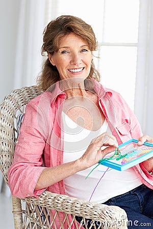 Senior woman sat doing cross stitch