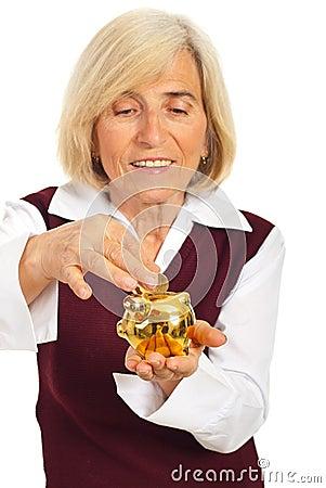 Senior woman saving money in piggybank