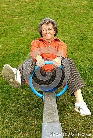 Senior woman on seesaw