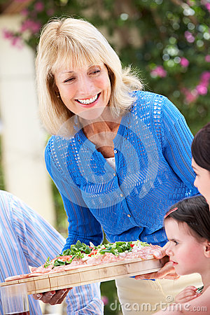 Senior Woman Serving A Family Meal