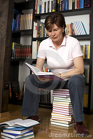 Senior woman sitting on book stack