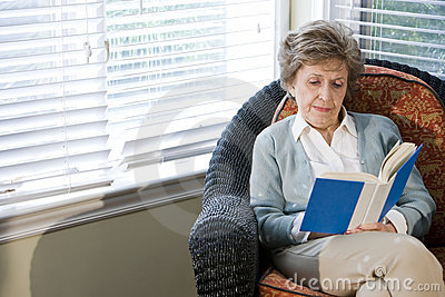 Senior woman sitting on living room chair reading