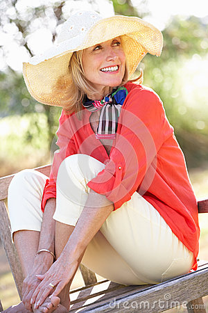 Senior Woman Sitting Outdoors On Bench