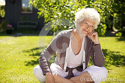 Senior woman sitting outdoors lost in thoughts