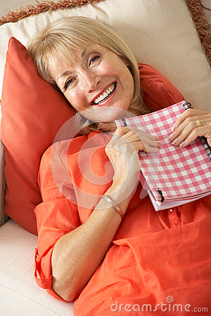 Senior Woman Sitting On Sofa Reading Diary