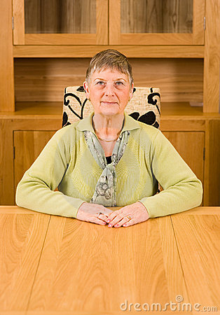 Senior woman sitting at table with copyspace below