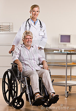 Senior woman sitting in wheelchair with doctor