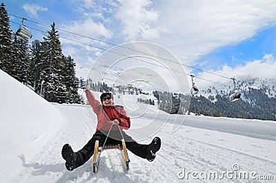 Senior woman on sledge having fun