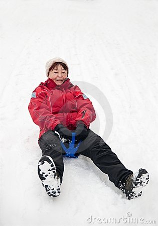 Senior woman on sledge - winter snow activity