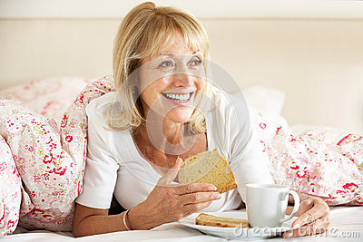 Senior Woman Snuggled Under Duvet Eating Breakfast