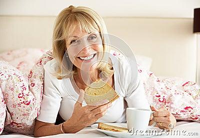 Senior Woman Snuggled Under Duvet Eating Breakfast