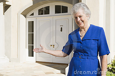 Senior woman standing outside home