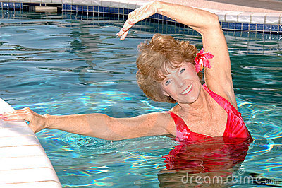 Senior woman stretching in the pool