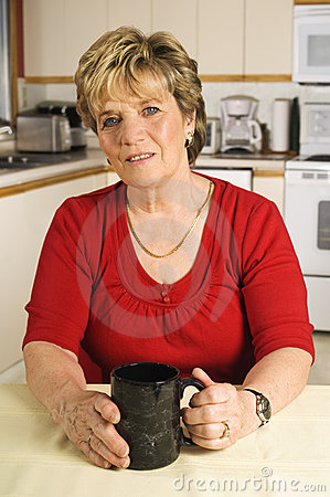 Senior woman taking a coffee break in her kitchen