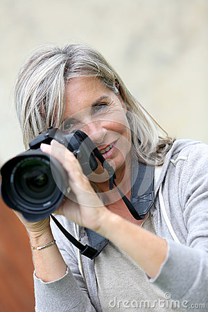 Senior woman taking pictures with a camera