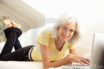 Senior Woman Using Laptop Relaxing Sitting On Sofa