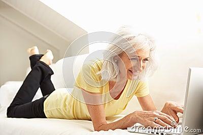 Senior Woman Using Laptop Relaxing Sitting On Sofa