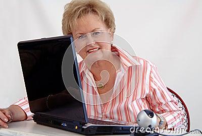 Senior woman using webcam