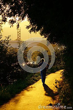 Senior Woman Walking Into Sunset