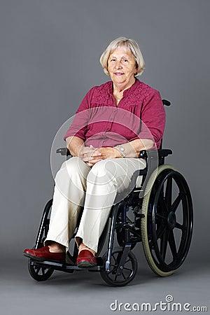 Senior woman in wheelchair over grey