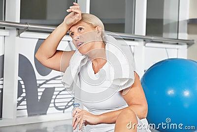 Senior woman wiping sweat of her