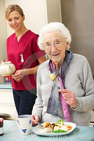 Free Senior Woman With Carer Eating Meal At Home Royalty Free Stock Photos - 24162028