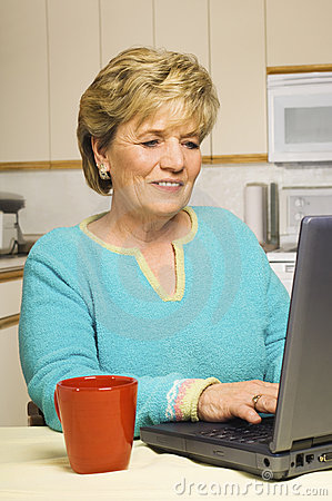 Senior woman works on her laptop in her kitchen