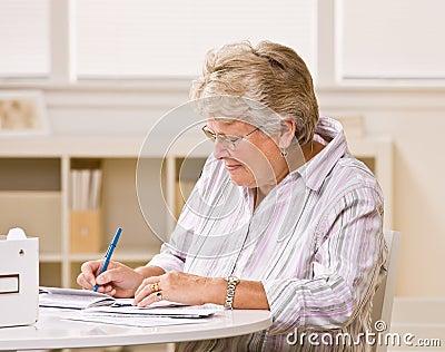 Senior woman writing checks