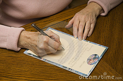 Senior woman writing a letter with pen and paper