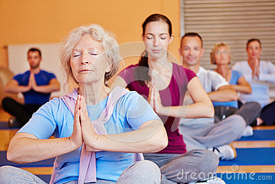 Senior woman in yoga class in gym