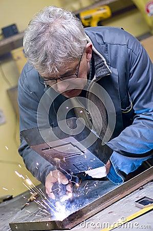 Senior worker welding