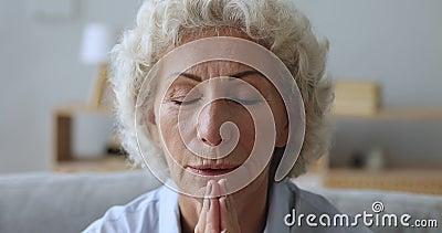 Senioralere Frau beten mit Hoffnung zu Hause, Nahaufnahme stock footage