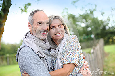 Seniors couple embracing each other in fields