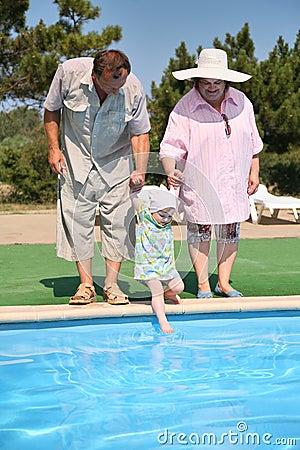 Seniors with girl near a pool