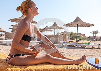 Sensous slim woman applying suntan oil