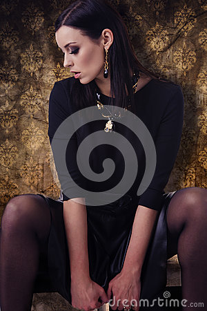 Sensual fashion model in black clothes with jewellery over golden pattern background