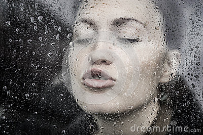 Sensual girl behind window in rain drops