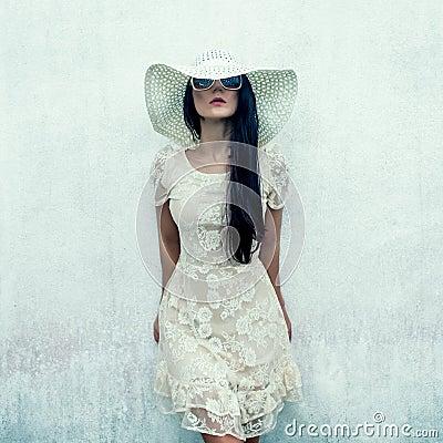sensual girl in a dress at a wall