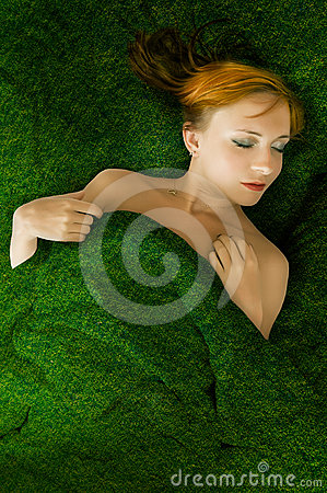 Sensual red haired girl in a grass bed
