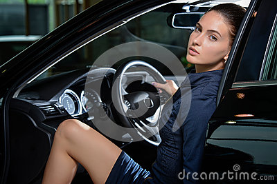 Sensual woman driver sitting inside her car relaxed