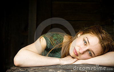Sensual woman relaxing in front of wooden barn