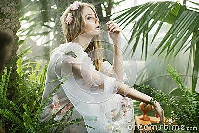 Sensual young lady among the greenery