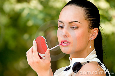Sensual young woman applying cosmetics on her lips