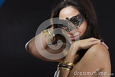 Sensuality.Beautiful young woman in mysterious black Venetian ma
