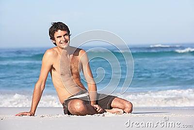 Sentada del traje de baño del hombre que desgasta joven