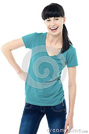 Señora de moda que presenta en estilo y que contellea una sonrisa