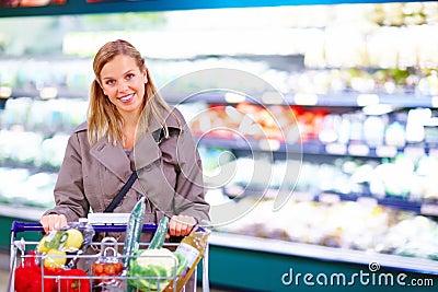 Señora que empuja una carretilla de las compras en un supermercado