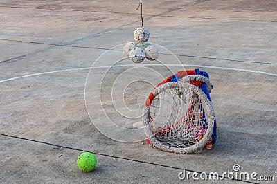 Sepaktakraw ball and hoop on concrete floor.