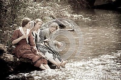 Sepia women by river creek in civil war reenactmen Editorial Stock Image
