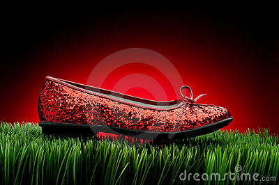 Sequined red slipper on green grass